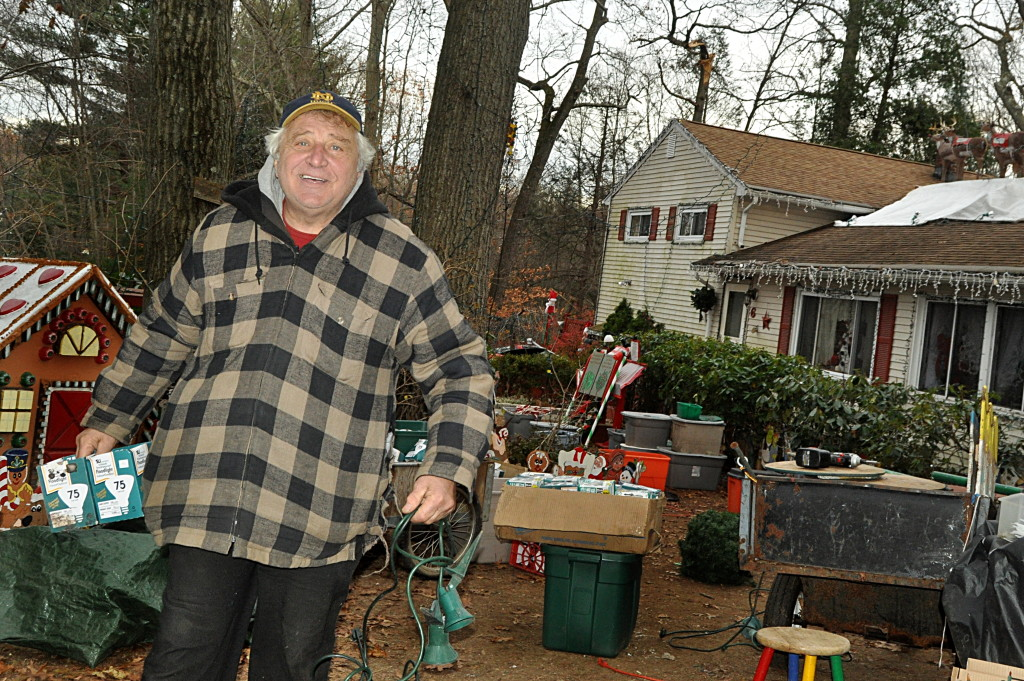 Rick Setti works in his front yard Thursday in Norwalk as he prepares Setti's Christmas Village for a Thanksgiving opening.