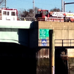 Norwalk fire engines sit on the Stroffolino Bridge Saturday morning as firefighters rescue a man who fell inside the bridge's inner workings. (Contributed)