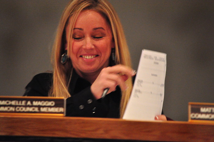 "Common Council member Michelle Maggio (R-District C) holds up a ""barrier"" to Norwalk Democrats briefly at Tuesday's meeting after it was announced that she is the new majority leader."
