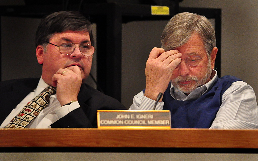 Norwalk Common Council members Matt Miklave (D-District A), left, and John Igneri (D-District E) listen to a debate at about 11 p.m. Tuesday at the Common Council meeting.