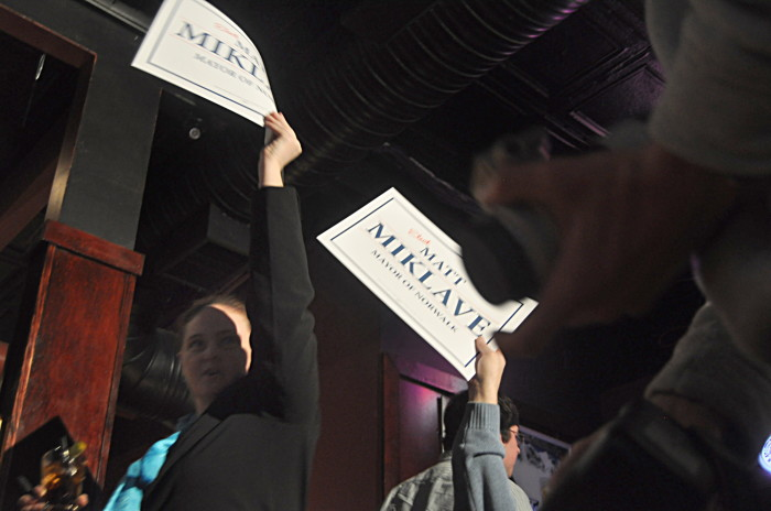Miklave for Mayor Communications Director Deb Goldstein holds up a campaign sign after Miklave's speech Saturday at Bradford's in SoNo.