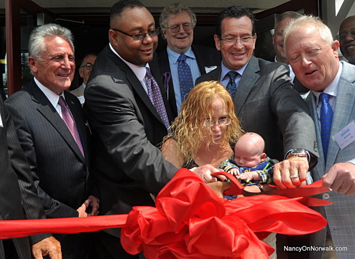"Robin DePaiva, center, cradles her 5-week-old son Patrick as she is surrounded by dignitaries Tuesday, in the ribbon-cutting for Gini's House. Around DePaiva are, from left, Mayor Harry Rilling, Liberation Programs President and CEO Alan Mathis, New Neighborhoods President and CEO Ross Burkhardt, Gov. Dannel Malloy and Bob Battle, son of Lou and Virginia ""Gini"" Battle."