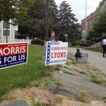 Campaign signs remind voters approaching the Columbus school who to vote for.
