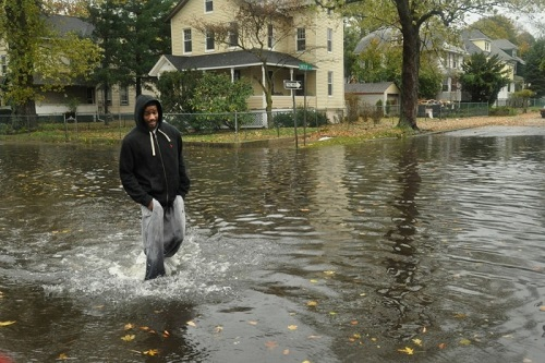 A Norwalk pedestrian crosses the intersection of Day and Burritt streets on Oct. 29, 2012, in flood waters brought by Superstorm Sandy.