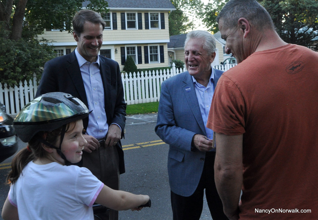 U.S. Rep. Jim Himes (D-Greenwich) and Norwalk Mayor Harry Rilling joke with a young East Norwalk resident, and her neighbor Wilfredo Perez, Monday on Pine Hill Avenue.