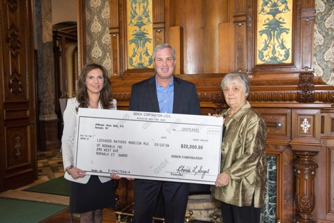 LMMM Executive Director Susan Gilgore, left,  and Chairman of the Board Patsy Brescia received a major grant donation from Xerox Foundation President Mark Conlin in the Museum's Library on April 28. (Sarah Grote Photography)