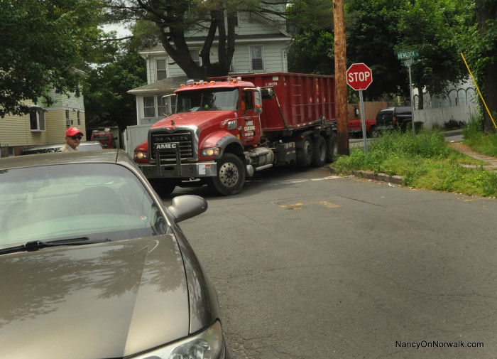 An AMEC Carting truck backs up Saturday after being unable to make the turn from Hemlock Place onto Chestnut Street due to a parked car.