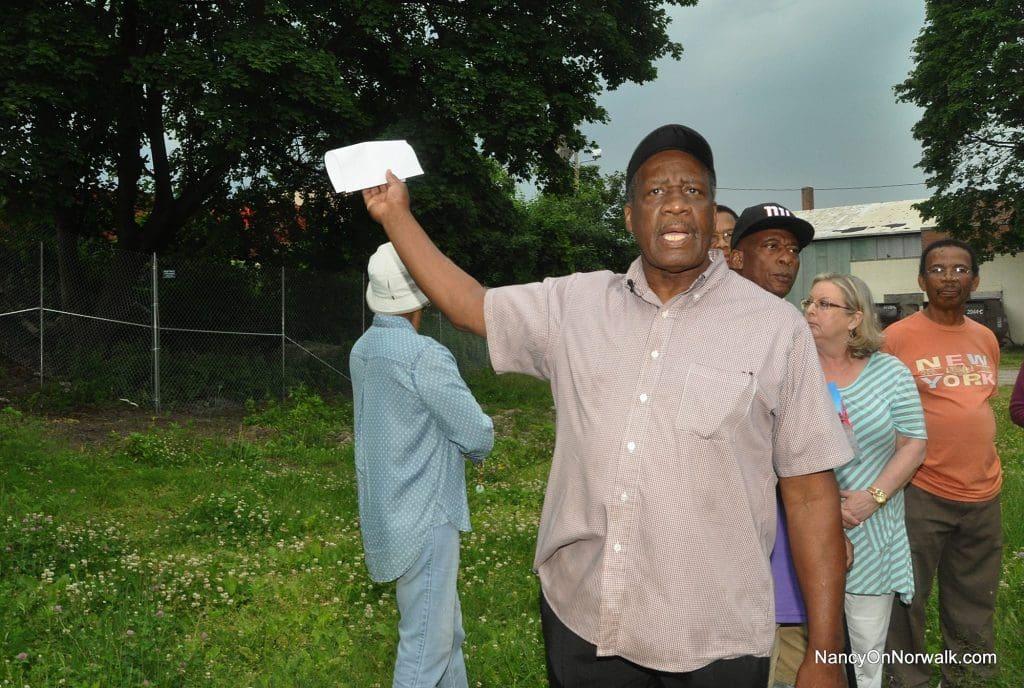 South Norwalk activist Ernie Dumas gestures Saturday toward a hill he said AMEC Carting LLC plans to blast to cut it down 30 feet.