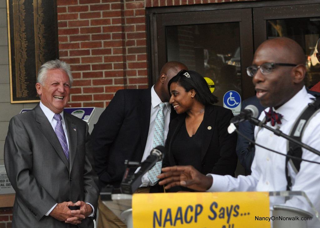Mayor Harry Rilling, left, reacts as Norwalk Branch NAACP President Darnell Crosland, right, elaborates on a story told by Rilling, at Tuesday's NAACP rally at City Hall.
