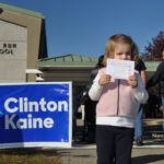 Reed Colbert, 3 1/2, marks an historic election by having her photo taken Tuesday at Fox Run Elementary School, at the request of her parents. Volunteers working the polls said three or families stopped in front of the Clinton/Kaine sign to take a photo.